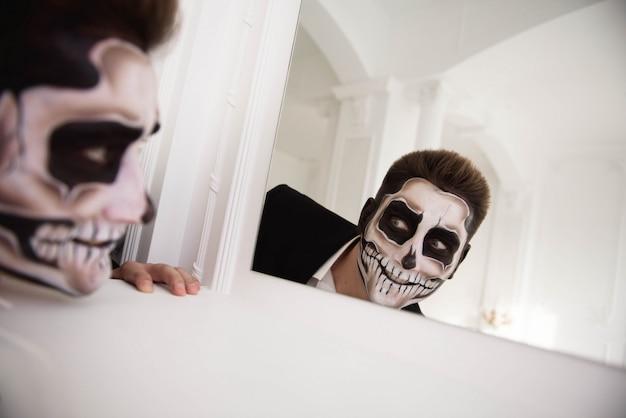 Hombre con maquillaje halloween. dibujando un vampiro, esqueleto