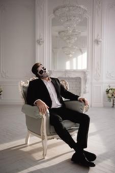 Hombre con un maquillaje terrible en el fondo de la habitación blanca.