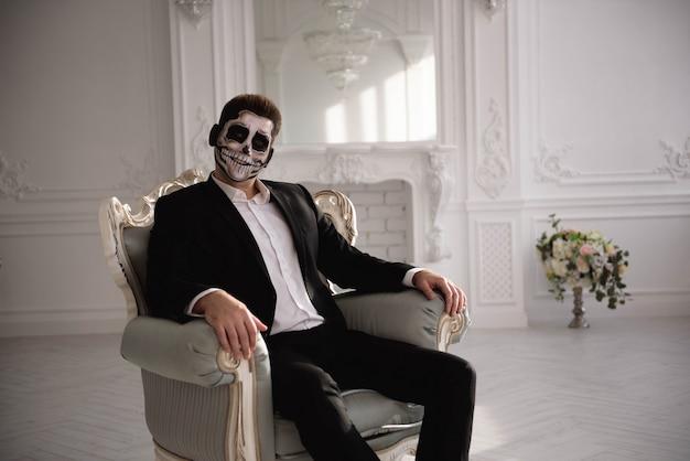 Hombre con un maquillaje terrible en el fondo de la sala blanca.