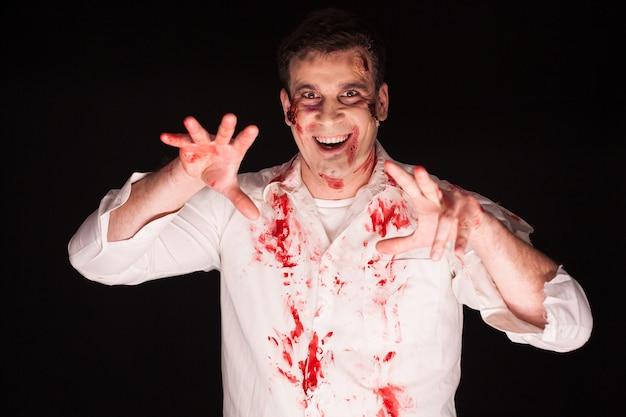 Hombre con un maquillaje de terror loco sobre fondo negro para halloween.