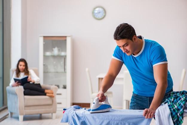 Hombre marido planchado en casa ayudando a su esposa