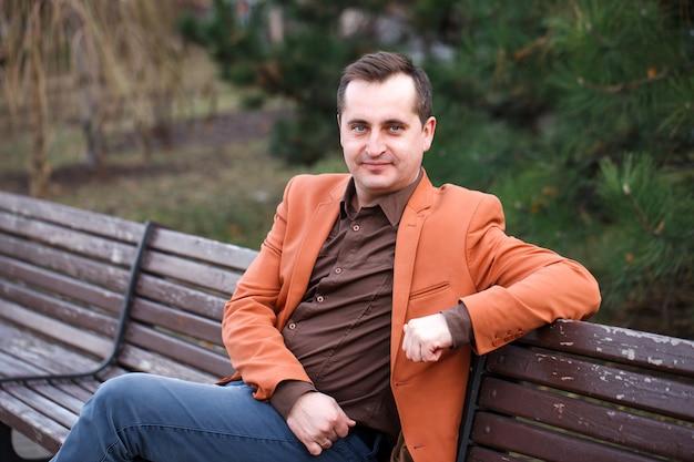 Un hombre de más de 40 años con problemas de calvicie está sentado en el banco.