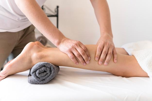 Hombre masajeando las piernas del cliente