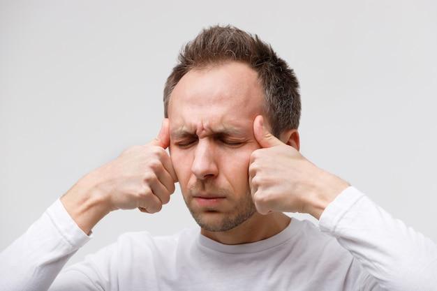 Hombre masajeando sus sienes, sufriendo de tensión nerviosa