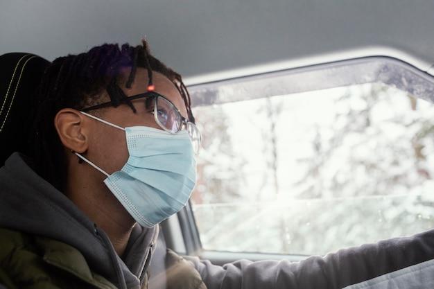 Hombre con máscara conduciendo