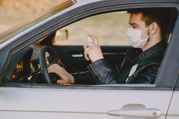 El hombre en una máscara desinfecta el auto