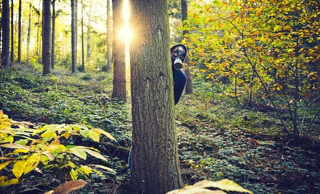 Hombre con máscara de gas en el bosque al amanecer.