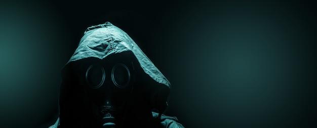 Hombre de la máscara de gas en el capó, sobre el fondo oscuro, soldado de supervivencia después del apocalipsis