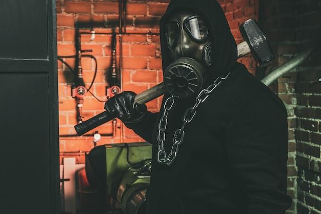 Hombre con máscara de gas y un martillo en la sala de máquinas. concepto de peligro nuclear, biológico y químico.