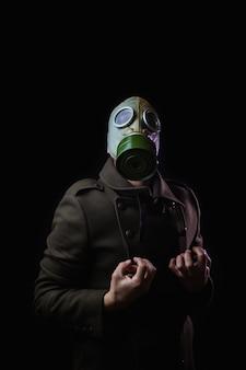Hombre con máscara de gas en posición de dolor sobre fondo negro