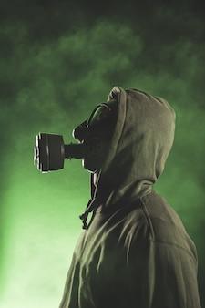 Hombre con máscara de gas sobre fondo verde con humo