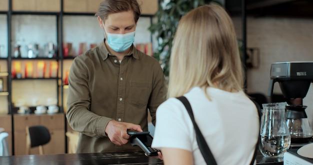 Hombre con máscara de loco pagando café usando tecnología nfc con teléfono y tarjeta de crédito, pago sin contacto con estudiante después de la pandemia de cuarentena por coronavirus.