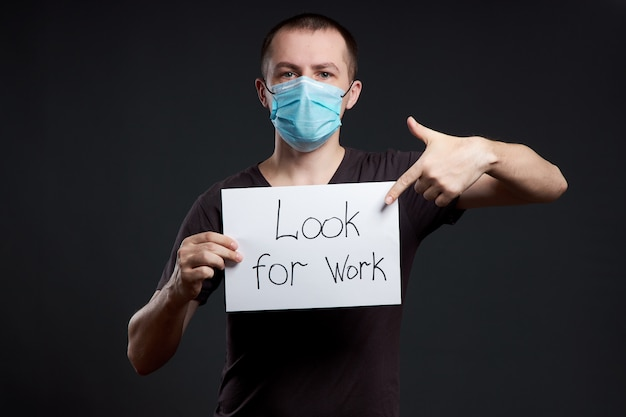 Hombre en una máscara médica con un cartel con las palabras buscar trabajo