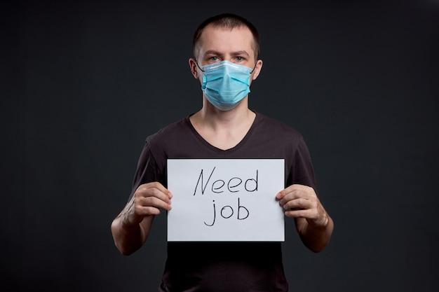 El hombre en una máscara médica con un cartel con las palabras necesita trabajo