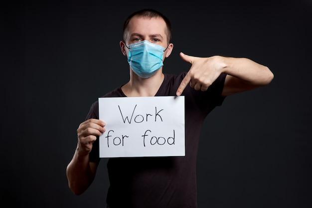Hombre en una máscara médica con un cartel con las palabras trabajar por comida