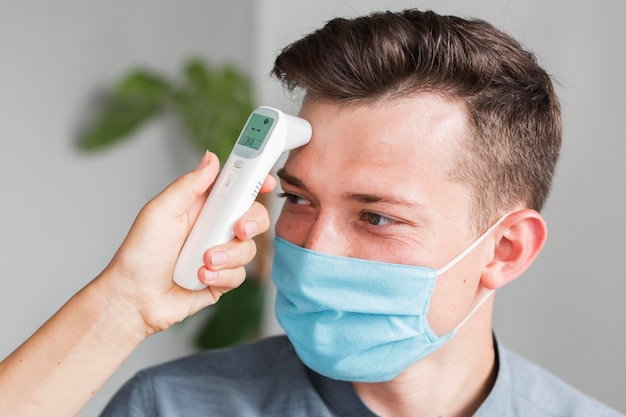 Hombre con máscara médica comprobando la temperatura en la oficina con termómetro