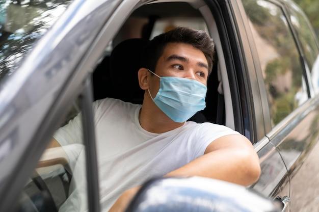 Hombre con máscara médica conduciendo