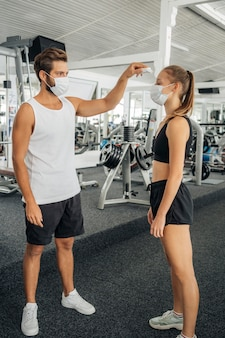 Hombre con máscara médica controlando la temperatura de la mujer en el gimnasio