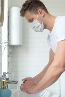 Hombre con máscara médica en el interior lavándose las manos
