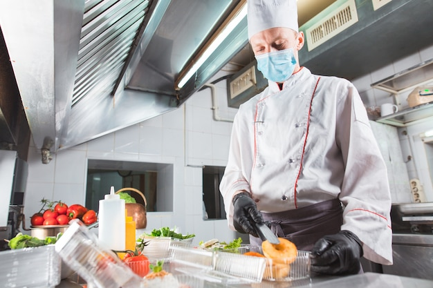 Hombre en una máscara médica de pie en una cocina
