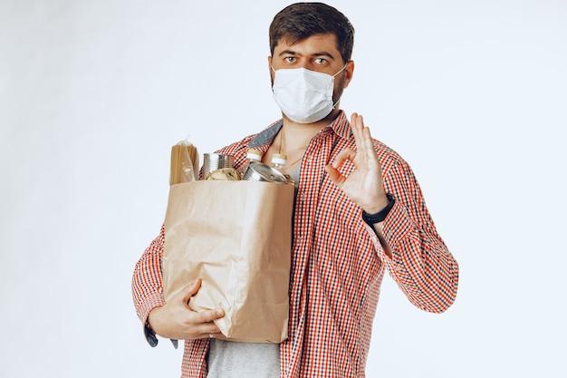 Hombre con una máscara médica protectora con una bolsa de una tienda de comestibles. entrega de comida
