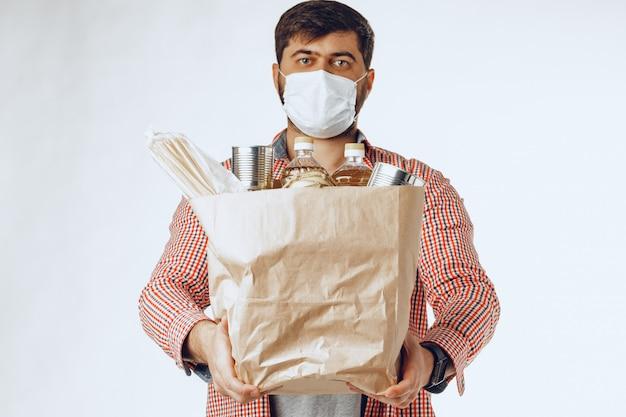 Hombre en una máscara médica protectora con una bolsa de una tienda de comestibles