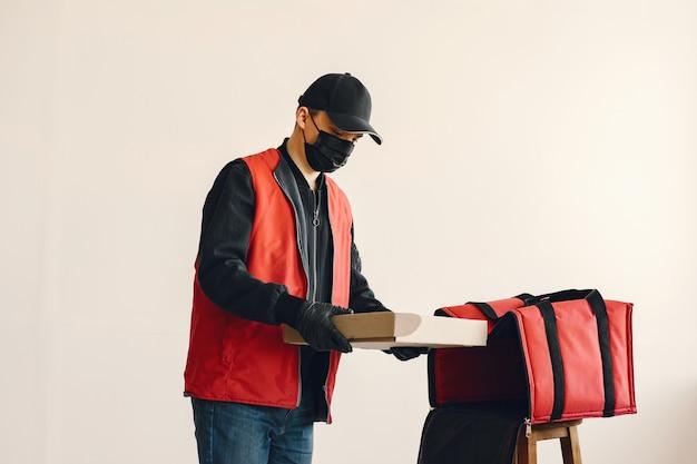 Hombre con máscara médica quirúrgica en uniforme con cajas