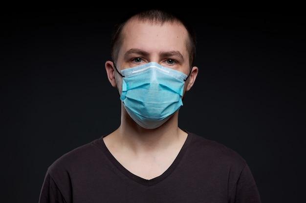 Hombre en una máscara médica sobre un fondo oscuro