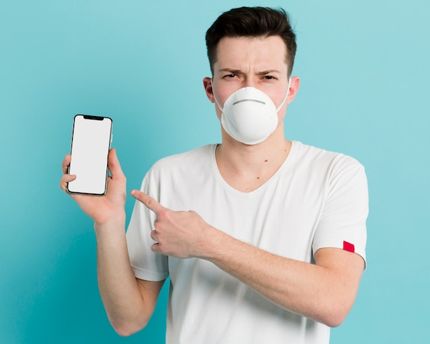 Hombre con máscara médica sosteniendo y apuntando a su teléfono inteligente