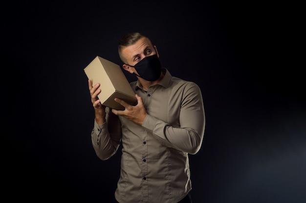 Hombre con máscara con paquete sobre pared negra