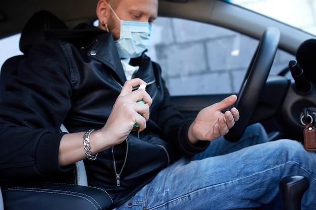 Hombre con máscara de protección sentado en el automóvil, rociando las manos con desinfectante antibacterial en aerosol para prevenir el coronavirus