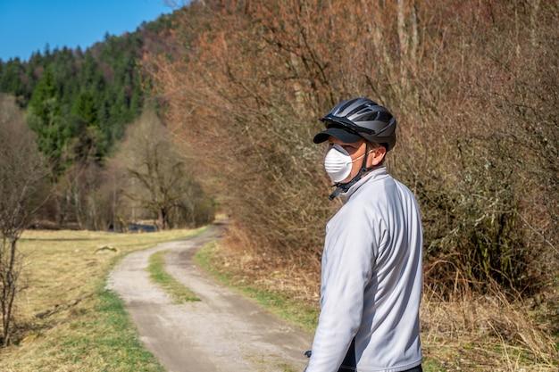 Hombre con máscara protectora en la cara montando bicicleta durante el coronavirus / covid-19