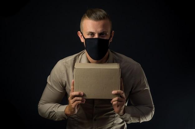 Hombre con máscara protectora con paquete sobre pared negra