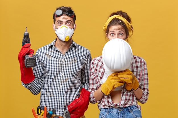 Hombre con máscara protectora de pie con taladro y mujer escondida bajo casco blanco renovando su piso trabajando juntos usando instrumentos de construcción. trabajadores de la construcción mejorando algo en la habitación