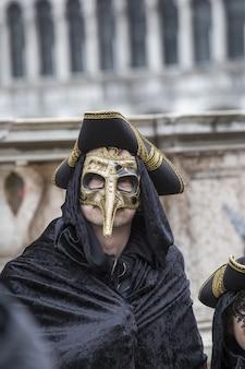 Hombre con una máscara tradicional de venecia durante el carnaval de fama mundial