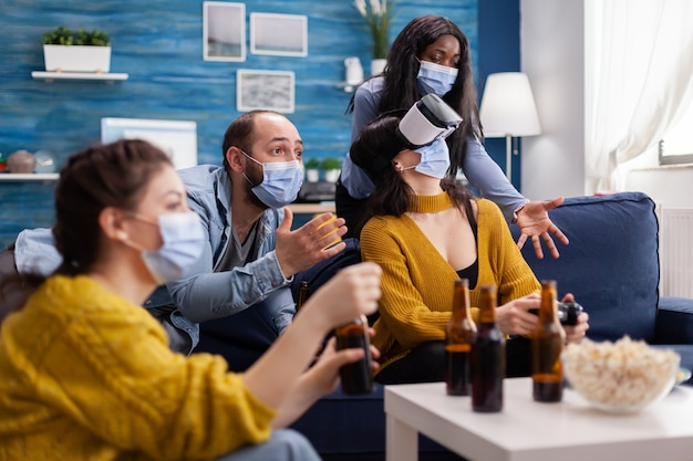 Hombre con mascarilla animando a amigos jugando videojuegos con auriculares vr en la sala de estar de casa manteniendo el distanciamiento social en tiempos de pandemia global con covid. gente multiétnica divirtiéndose.
