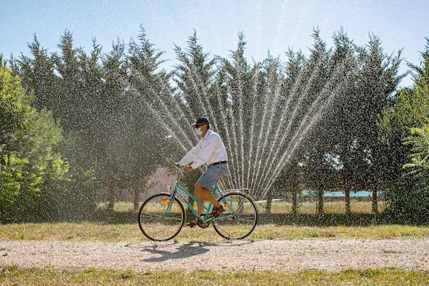 Hombre con mascarilla en bicicleta azul pasando por riego automático en el jardín