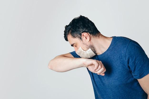 Hombre en la mascarilla estornudos