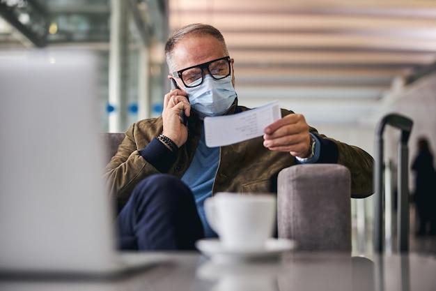Hombre con una mascarilla llamando a su teléfono inteligente