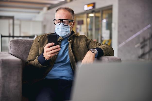 Hombre en una mascarilla mirando su gadget