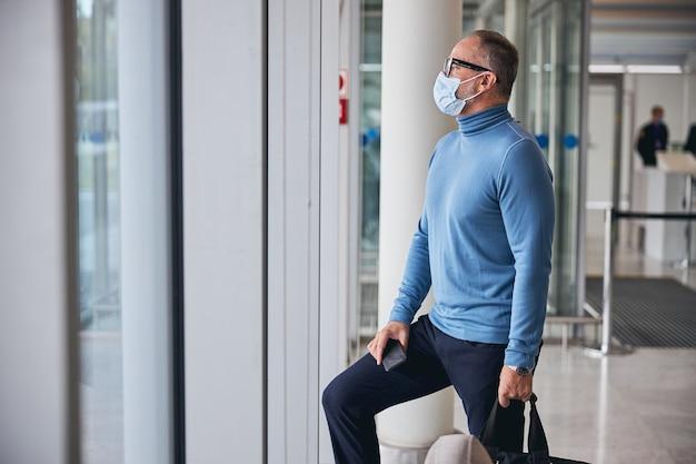 Hombre en una mascarilla de pie en la terminal del aeropuerto