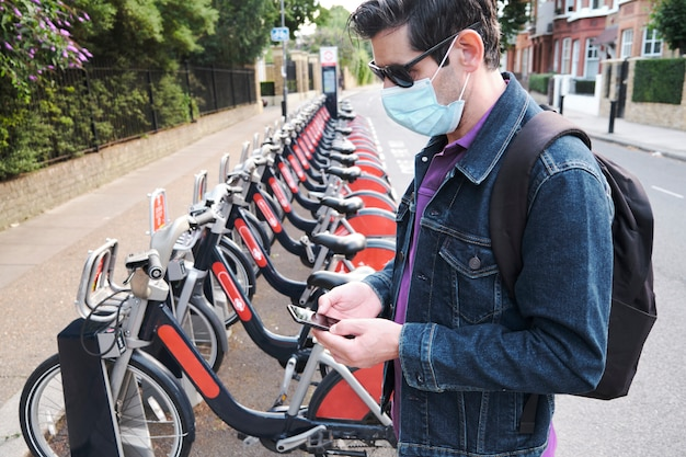 Hombre con una mascarilla protectora usando un teléfono inteligente frente a bicicletas eléctricas de alquiler