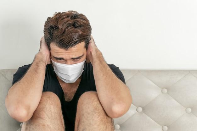 Hombre con mascarilla para proteger la sensación de malestar dolor de cabeza y tos debido al coronavirus covid-19 en la sala de cuarentena