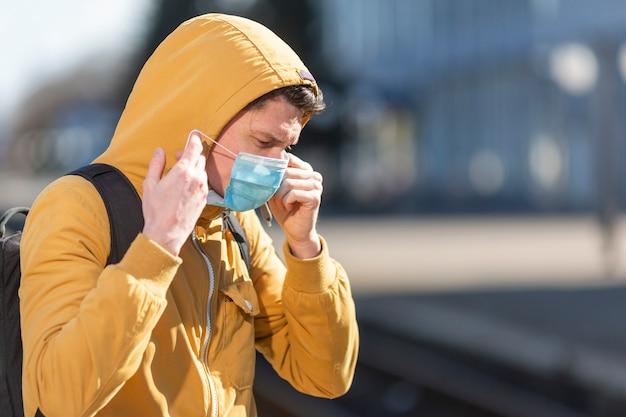 Hombre con mascarilla quirúrgica al aire libre