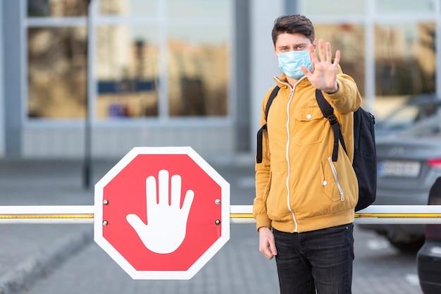 Hombre con mascarilla quirúrgica con señal de stop