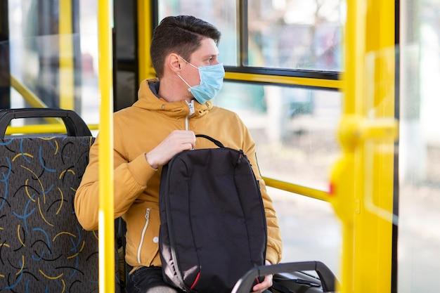 Hombre con mascarilla quirúrgica en transporte público