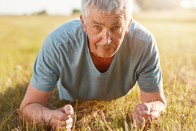 Un hombre mayor de unos 50 años hace flexiones de césped verde mientras se recrea en la naturaleza, no se olvida del deporte
