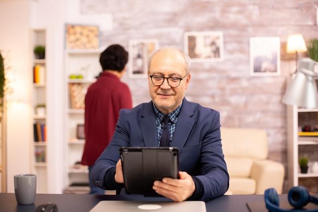 Hombre mayor de 60 años usando una tableta digital moderna en su acogedora casa