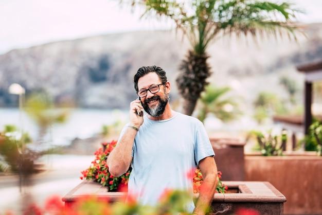Hombre mayor adulto alegre sonríe y hace una llamada telefónica mirando a la cámara