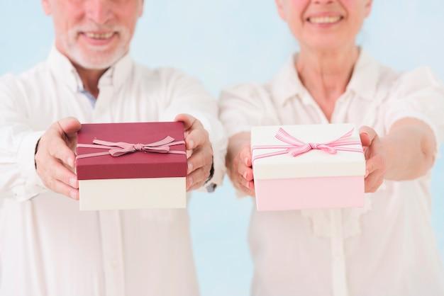 Hombre mayor alegre y mujer que dan la caja de regalo